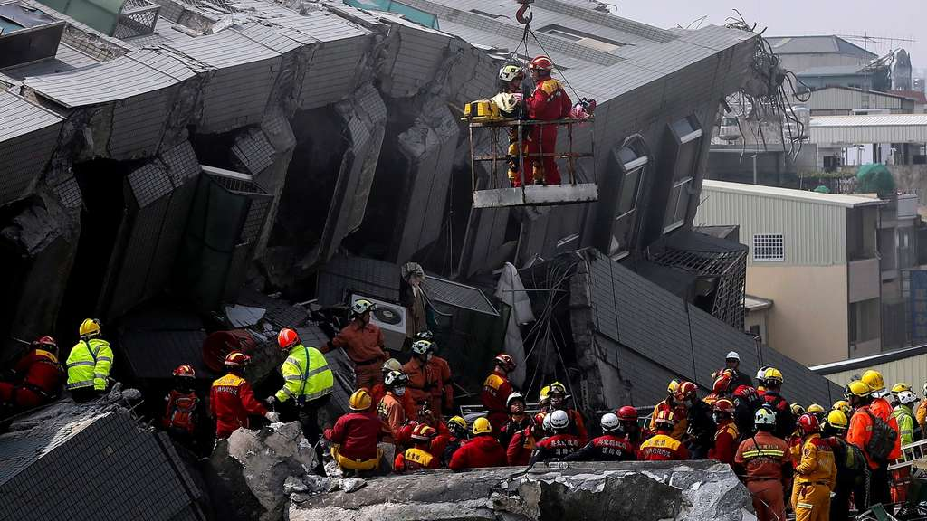 epa05145534 Rescuers use a crane to lift survivors from a collapsed building following a 6.4 magnitude earthquake that struck the area in Tainan City, Taiwan, 06 February 2016. At least five people, including an infant, were killed and dozens injured when a high-rise building collapsed after a 6.4-magnitude earthquake struck southern Taiwan early 06 February, authorities said. The 17-storey building in Tainan city was said to be home to about 200 people in 60 households, state-run media reported. Several other buildings in Tainan collapsed or were damaged by the quake that struck at 03:57 am local time (19:57 GMT Friday). EPA/RITCHIE B. TONGO +++(c) dpa - Bildfunk+++
