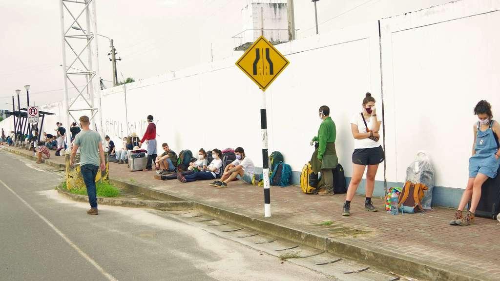 Warten mit Sicherheitsabstand: Während links im Hintergrund Militär patrouilliert, warten die Ausländer vor dem Flughafen, dass sie endlich aus dem Land kommen.